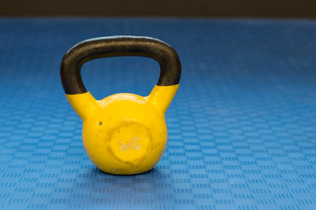 Small yellow eight kilograms heavy worn out kettlebell Stock Photo