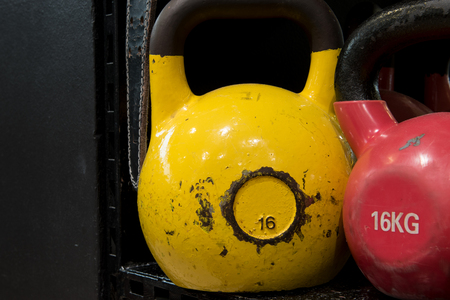 Red and yellow worn out kettlebells on a black metal shelf in a gym