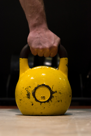 Strong human hand holding worn out yellow kettlebell in a gym on a wooden floor with black background Stockfoto