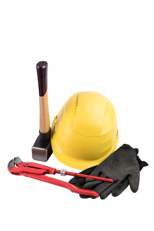 Yellow safety helmet with a sledgehammer with wooden handle, working gloves and adjustable plumbers wrench isolated on a white background, surface. Path saved, cut out. Construction equipment.