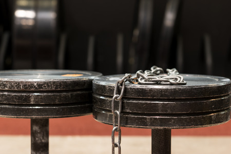 Two old and used gym black metal dumbbells with silver chain. Gym equipment Stock Photo