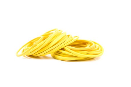 Pile of yellow rubber bands isolated on white background. Packaging supplies and accessory. Thin rubber bands. Stock Photo