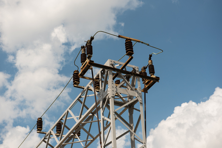 Train or railway power line support. Railway power lines with high voltage electricity on metal poles against blue sky. Stock Photo