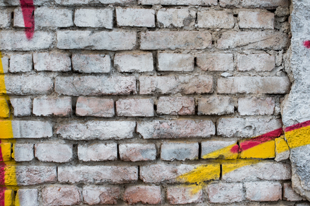 Old painted white brick wall with yellow and red graffiti details. White background Banco de Imagens