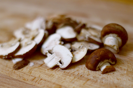 Whole agaricus brown button,portobello,mushrooms,sliced and chopped in the kitchen on a wooden chopping board ready to be used in cooking or salads, in vegetarian and vegan cuisine.