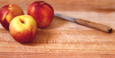 Fresh, organic apricots on a wooden chopping board with a kitchen knife besides them.