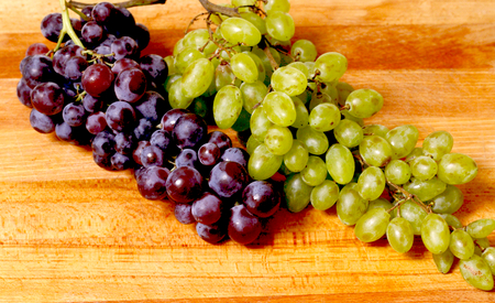 Beautiful,organic,fresh green and red grapes isolated shot on wooden background.