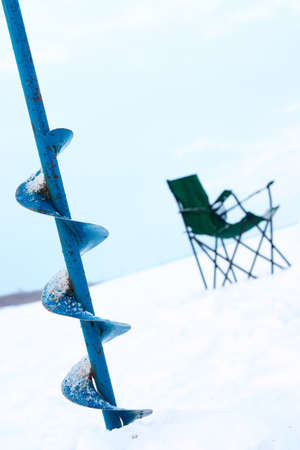 drill for ice and a chair for winter fishing on the lake photo