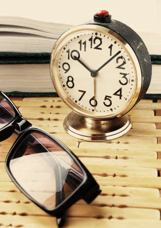 book with alarm clock and eyeglasses photo