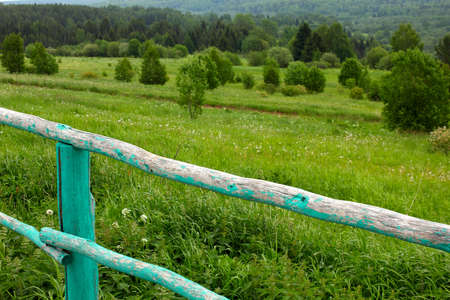 summer landscape with an old wooden fence in the foreground photo