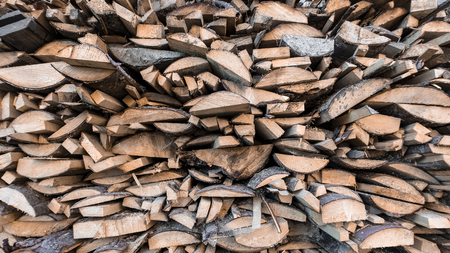 Crushed wood. Firewood stacked on each other in rows. Front view, close-up, background