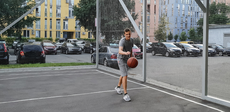 young blond man in gray sportswear playing basketball on the open basketball court Фото со стока