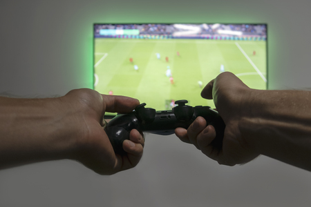 Man hold gamepad in hands in front of  tv screen with Pro Evolution Soccer. One gamer. Widescreen tv hanging on the wall
