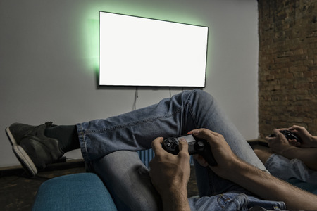 Two men playing video game. Clean monitor mockup. Hands holding console controller. Blank tv screen mock up. Widescreen tv hang on the wall. Stock fotó