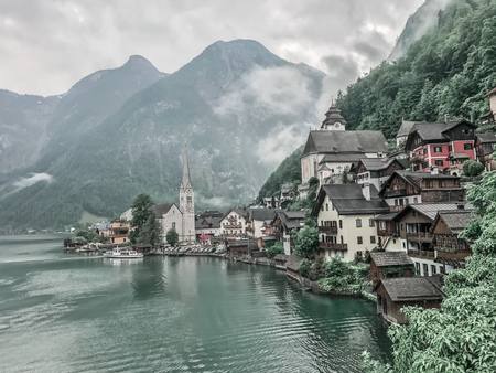 lakeside town, Hallstatt, Austria. Church on the shore of the lake on the background of mountains and houses, Houses among the trees