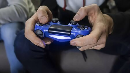 Man hold the console controller in hands, playing game. One gamer person, close-up of man's hands