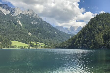 Beautiful views of the crystal clear mountain lake with mountains in the background. covered with trees and snow tops, blue sky with massive white clouds Archivio Fotografico
