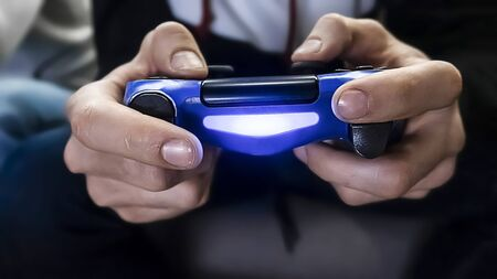 Man hold the gamepad in hands, playing game. One gamer person, close-up