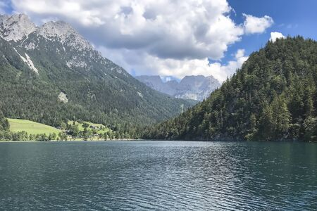 Gorgeous views of mountain peaks covered with snow and forests on the background of clear, calm lake, the sky covered with massive clouds, Sunny summer day Archivio Fotografico