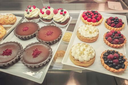 cakes with different fillings and colored glaze, decorated with fruits and berries behind the shop window Archivio Fotografico