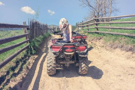 Young woman in hat sitting on a red ATV on a rural road on a Sunny day, a wooden fence along a rural road