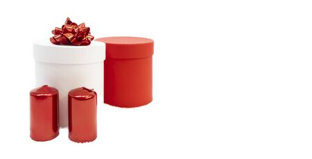Cylindrical red holiday gift box, white cylindrical gift box with a red bow for woman on white background with red candles, Valentine's day, Christmas or mother day, women's day. Holiday concept.