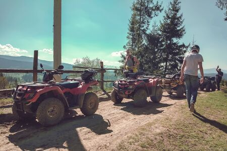 A string of Quad bike on a rural road on the background of mountains and fir trees, people made a stop in the tour