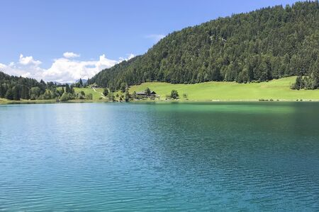 Big blue lake amid the green forest of the mountains on a warm Sunny day. Austria