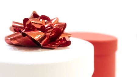 Closeup of gift boxes on white background. White box of cylindrical form with a red bow and red box. St. Valentine's Day, International Women's Day, birthday, holiday concept, mock up Archivio Fotografico
