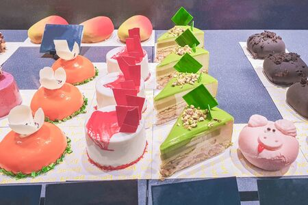 cakes with different fillings and colored glaze, decorated with fruits and berries behind the shop window, a sweet dessert Archivio Fotografico
