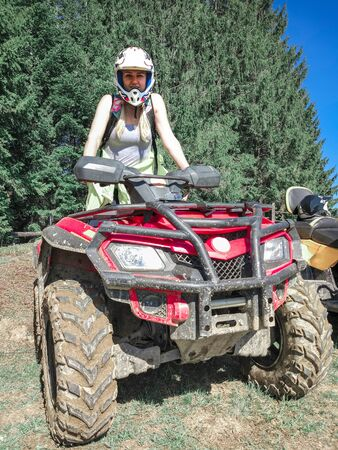 Young woman in helmet on a red Quad bike in a forest
