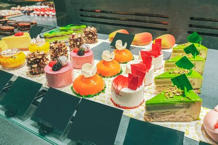cakes with different fillings and colored glaze, decorated with fruits and berries behind the shop window, colorful desserts Archivio Fotografico