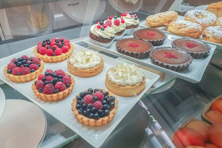 cakes with different fillings and colored glaze, decorated with fruits and berries behind the shop window, sweet and colorful dessert