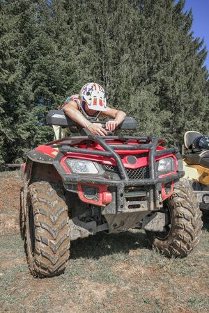 A young woman in a helmet for security configures the action camera on the hood of the red ATV in the background of the trees Archivio Fotografico