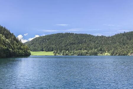 A large scenic lake on the background of green mountains on sunny summer day, Austria