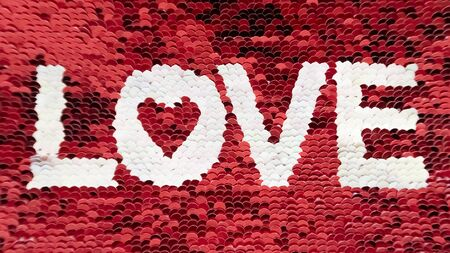 The inscription love sequins in white on background of red sequins. The concept of feeling, relationships.
