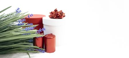Festive cylindrical gift boxes with bow, red candles and blue flowers on white background, greeting card for holiday, copy space, Valentine's Day, International Women's Day, birthday, holiday concept