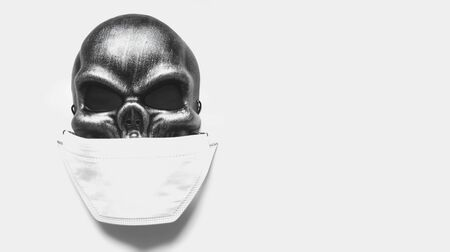 Dark gray skull mask with a bandage on his face. The concept of coronavirus. Death from the pandemic. The risk of disease