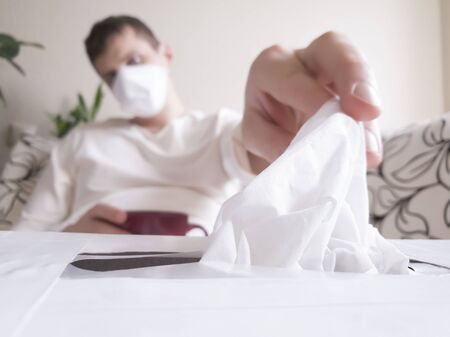The outbreak of the flu or a cold. Young Caucasian man in a mask on the face reaching for a disposable cloth in the box. Close-up tissue box