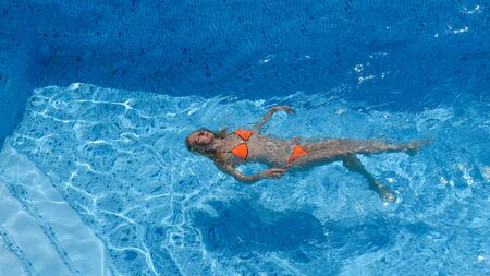 Summer, vacation, slim young girl lying on her back in a pool in an orange bikini, top view. Clear blue water