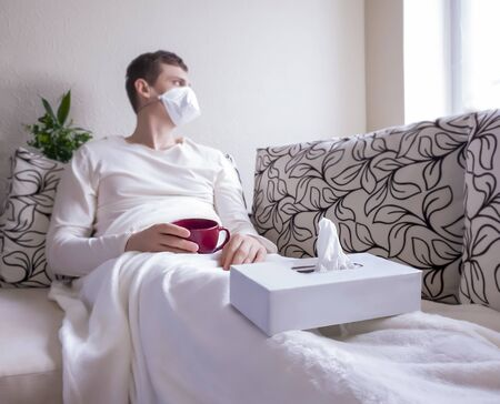 The concept of a cold or seasonal flu. A young man in a mask looking out the window, lying on the couch. Drinking hot medicinal drink. Quarantine
