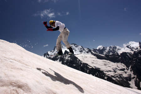 Snowboarder in the mountains, summer skiing on the board