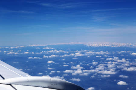 Wing of the plane on blue sky background and snowy mountains below, view from window of a jet plane wing with beautiful weather photo