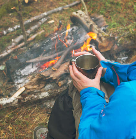 travel mug: Travel girl drinking from a mug. Lunch during the journey to the wild. Camping hiking lifestyle.