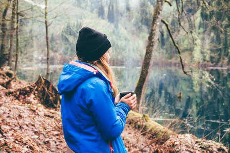 tomando café: Muchacha del recorrido que bebe de una taza en el fondo del bosque y el lago de montaña. Chica de vacaciones disfrutando de la belleza de la naturaleza. Acampar estilo de vida senderismo.
