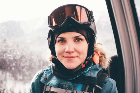 oncept: Happy girl on ski resort. Snowboarder on vacation. Lifestyle Concept Adventure winter physical activities.