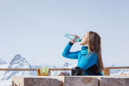 A woman snowboarder drinking water outdoors against a background of snowy peaks. Travel Lifestyle concept active leisure in the open air of winter sports. Sport in the winter mountains.