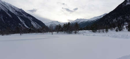Winter panorama of the mountain with valleys and forest. Caucasus. Landscape of high peaks in clear weather. The concept of travel and leisure, winter sports, lifestyle, adventure.