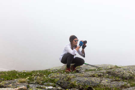 A young hipster girl with a camera in hand on a background of a misty rocky landscape. The concept of adventure, travel, entertainment and hobbies.