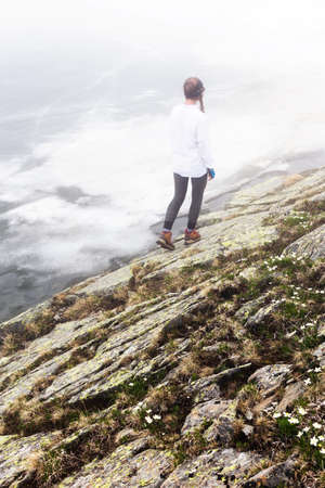 A girl outdoors travels against the background of an epic landscape with rocks and a lake in the fog.